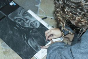 Senior, Audrey Schminger, puts her final touches on her artwork.