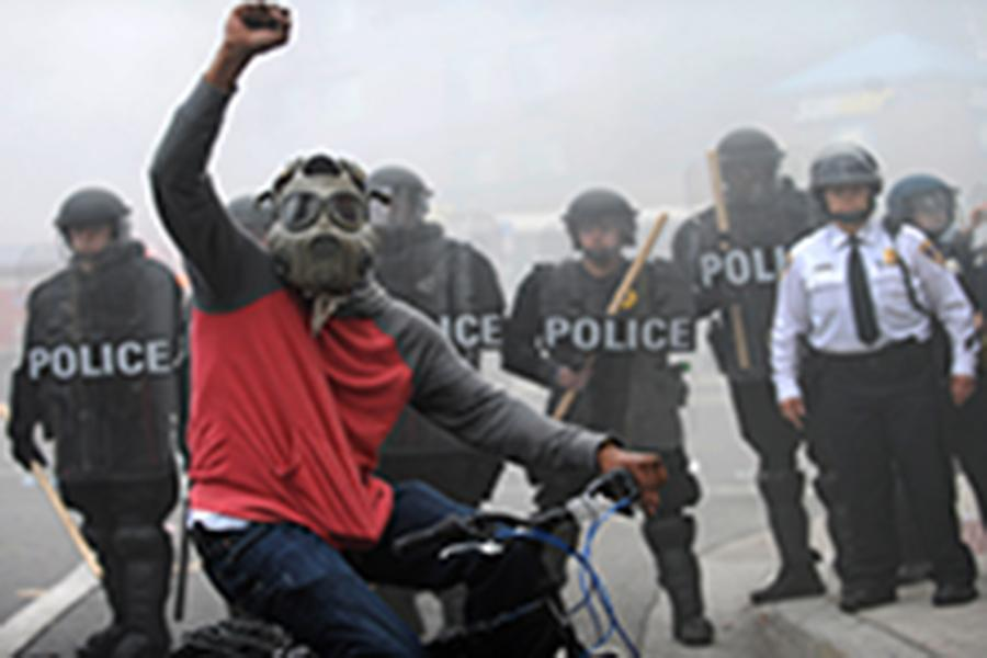 A protester rides his bike in front of a police line at North and Pennsylvania Avenues on Monday, April 27, 2015, in Baltimore. (Algerina Perna/Baltimore Sun/TNS)
