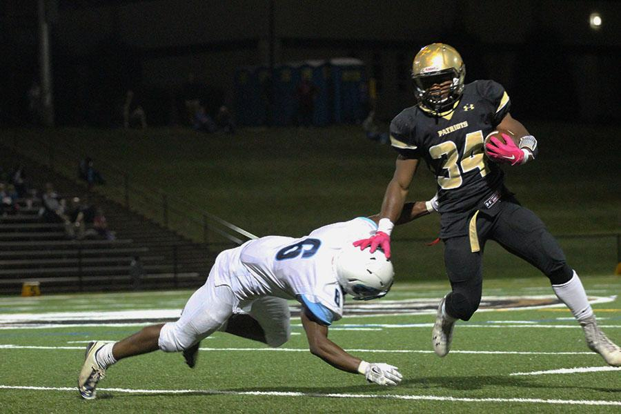 Varsity running back junior Devin Darrington stiff-arms a defender to the ground during the game. The Patriot's offense scored 41 points against Pallotti and defeated them 41-0.