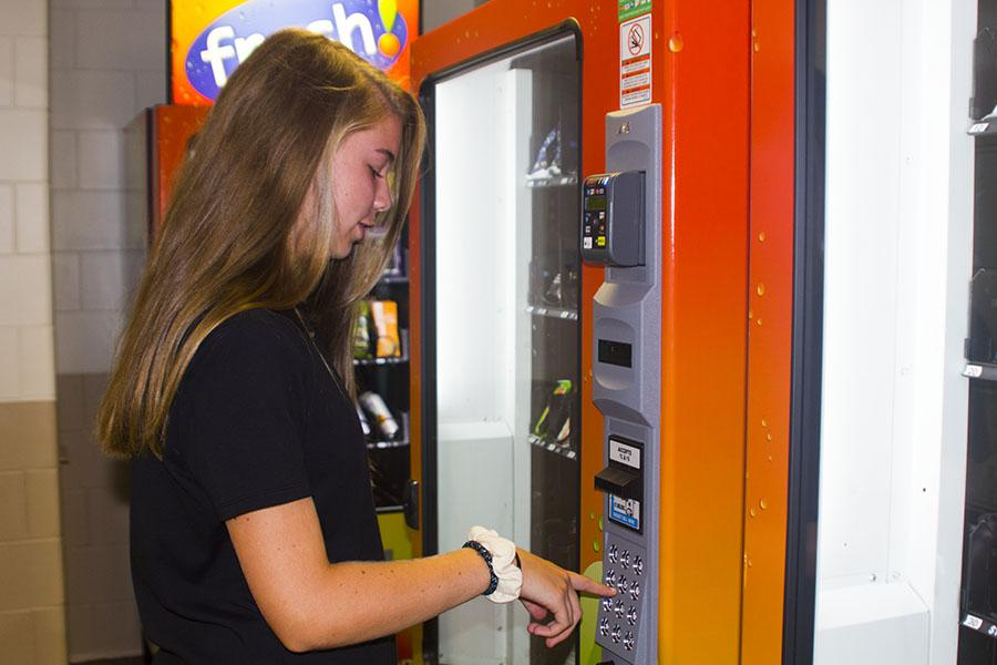 Freshman Ellie Bruggeman stops for a snack at the new healthy vending machines. The machines were installed over the summer in an effort to promote healthy snacking.