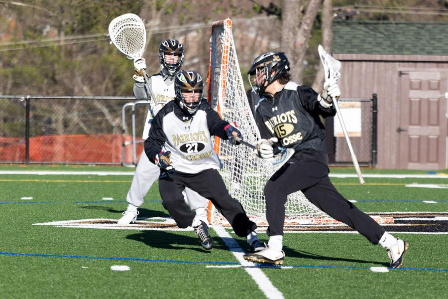 Sophomore defenseman Henri Marindin meets senior attackman Chris Tassanari at the goal line during drills in practice. The varsity lacrosse team is striving for a championship season to achieve the three-peat in the MIAA B Conference.