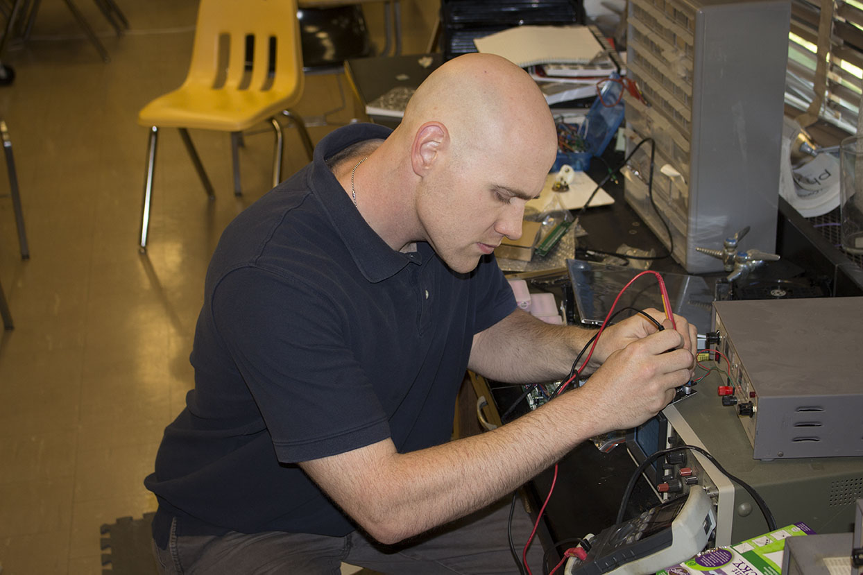 Physics teacher Anthony Davidson focuses as he tests computer equipment for a freshman building a gaming computer. This is Davidson's second year at JC, and he enjoys helping students in class as well as with their personal endeavors.