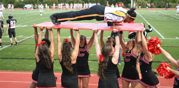 Sophomore Ola Ekundayo performs push-ups on a board held aloft by Catholic Univeristy cheerleaders.  Tradition dictates that after every touchdown, a volunteer does push-ups for however many points the team has.