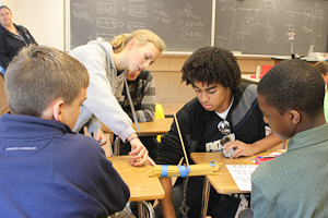At last years STEM night, AJ Stewart, class of 12, and Heather Kirwan, class of 12, help middle school students perform scientific experiments. This year, STEM night will be held on Tuesday, Oct. 9.