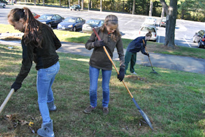 Sophomores Erin Cadden (left) and Elizabeth Driver (center) share a laugh as they rake leaves on Volunteer Day, while junior Abbie Swanson (right) helps out.