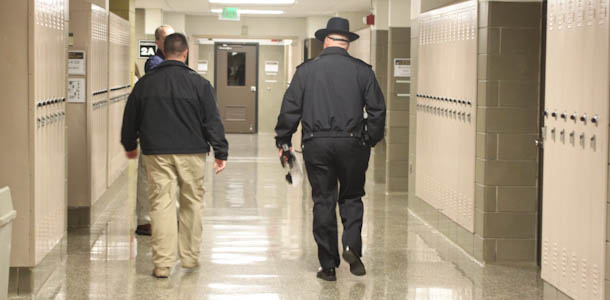 Police officers walk through the hallways ensuring that classrooms are sufficiently locked down in JC's first practice of the new lockdown drill.