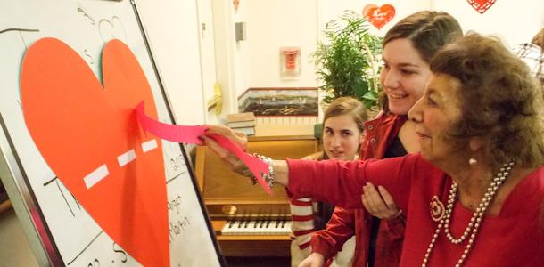 Juniors April Moscati and Kirsten Kyburz play Pin the Arrow on the Heart at the Rock Spring Village Nursing Home.  Romero club members celebrated Valentine's day with the elderly.
