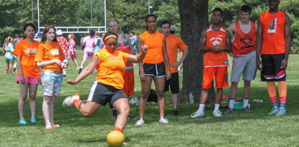 Senior Taylor Smith kicks for her team on field day during their kick ball game. Her team, standing behind her, watches and cheers her on.