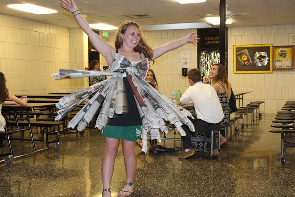 Senior Susie Snee models a newspaper dress for senior Emma Minnis's senior project.