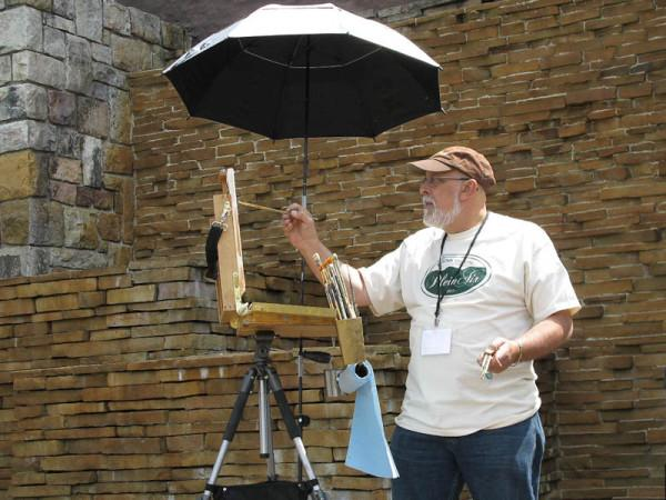 Art teacher Bruno Baran focuses on finishing his paintings at one of his competitions. He takes it very seriously and has done many contests over the years.