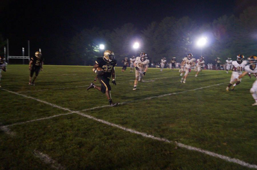 Paul Lorick '15 runs with the ball during the Friday night game against St. Paul's last year. JC played all their home conference games under the lights last season and will play in the first night game on senior night against Boys Latin.