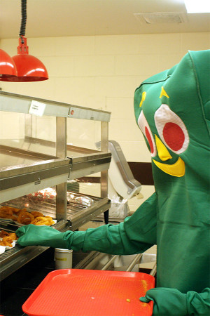 Online Chief and senior Cole Alban, dressed as Gumby, reaches for chicken tenders in the cafeteria. Alban wore the costume for all of Class Color Day, including lunch.