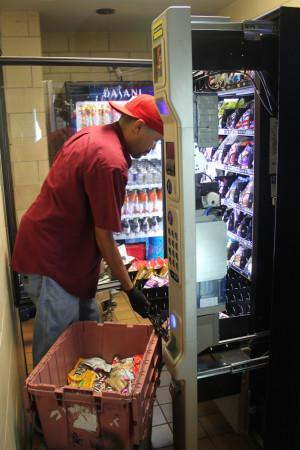 Ricardo Byrd works to refill the new vending machines after school. The new vending machines were put in on Sept. 27 to replace the old vending machines that used to sit there.