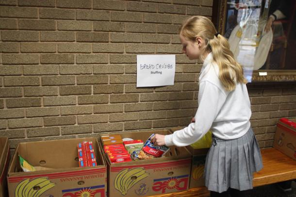 Junior Katie Benisch volunteers to sort nonperishable goods that were collected during the food drive. The food was donated to the food bank at St. Francis de Sales Church in Abingdon and the Manna House Soup Kitchen  in Bel Air.