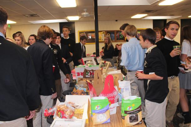 Freshmen reach for donuts during their second class breakfast on Dec. 4. The class meets quarterly during advisory for freshman class bonding.