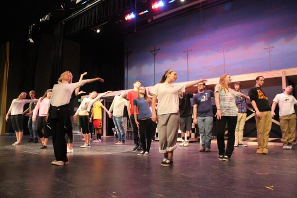 Director Kim Brueggemann leads the cast of Footloose in choreography. The first performance of the show will be held on Feb. 28.