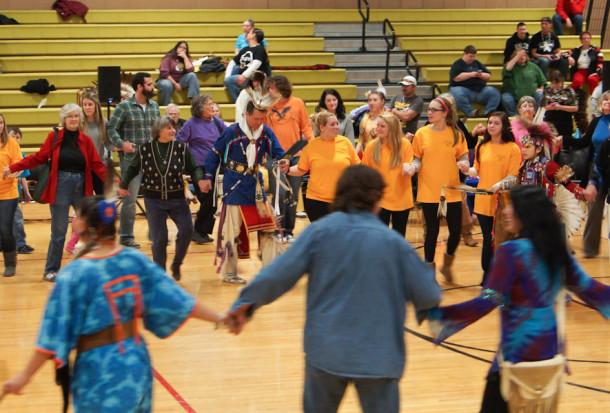 Academic Vice Principal Gary Scholl, and seniors Alexandra Kane, Caitlin Johnson, Julia Wilbert, and Sarah Owen dance around in a circle at the Morning Star Pow Wow at JC. Throughout the day, several types of Native American dances were performed.