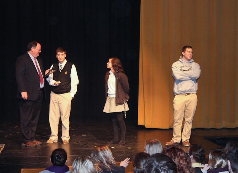 Seniors Taylor Gerber, Sarah Owen, and Clark Grube play a quiz game about finances with Athletic Director Larry Dukes. They were on stage in the auditorium at the Senior Seminar on Feb. 20.