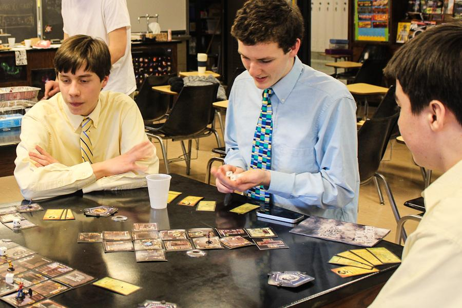 Sophomore Wilson Pais prepares to roll the dice during a game of Betrayal at House on the Hill with sophomore Matt Walker and junior Alex English. Game Club members play games during their meetings in science and robotics teacher Jessica Limmers classroom.