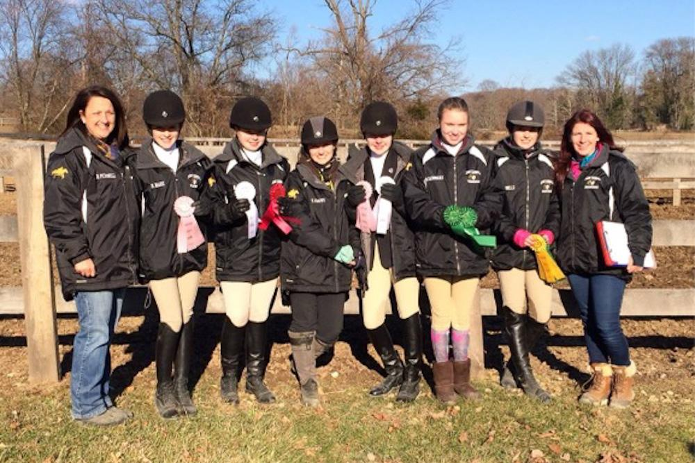 From left to right, head coach Dennise Petronelli poses with freshmen Brooke Hare, Mary Olsen, Taylor Crews, Alyssa Whitehead, Olivia Barnhart, captain Selina Petronelli, and her assistant coach Beth Hess with their ribbons after a show at Garrison Forest. Five members of the team qualified for regional due to the points they accumulated during the season.