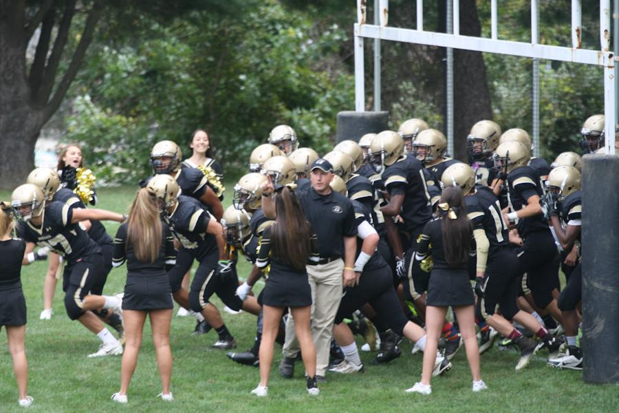 The+football+team+runs+out+on+the+field+wearing+the+traditional+gold+helmets+in+a+game+against+Delmarva.+The+administration+decided+to+keep+the+gold+helmets+instead+of+changing+to+black.+