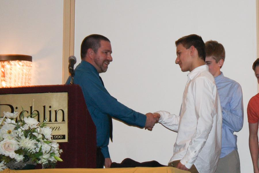 Freshman Steven Kutcher shakes Head Coach Robert Torres's hand as Kutcher receives his Triple Threat Award for men's JV indoor track. The Winter Banquet was held at the Richlin Ballroom on Tuesday, March 11.