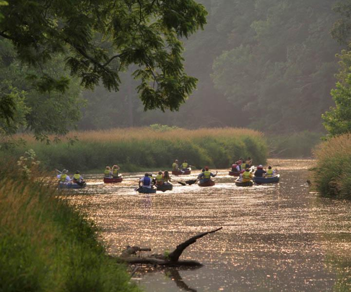 At Eden Mill Nature Center, a group of canoers row out onto the Deer Creek River. Eden Mill offers a multitude of outdoor activities to  experience at their property in Pikesville, MD.