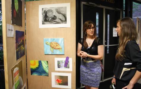 Juniors Annalee Gabler and Jessica Hastings look at Gabler's art board during the Fine Arts Show on May 15. The show exhibited the work of students in all art classes.