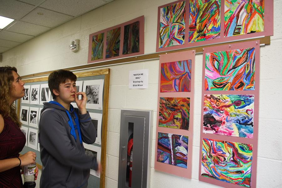 Junior Charlotte Molali and freshman Elliot Wilson discuss Wilsons art collection. The collection, called Watch Me Boil, consisted of drawings with oil pastel crayons and watercolor paints on colored and white paper.