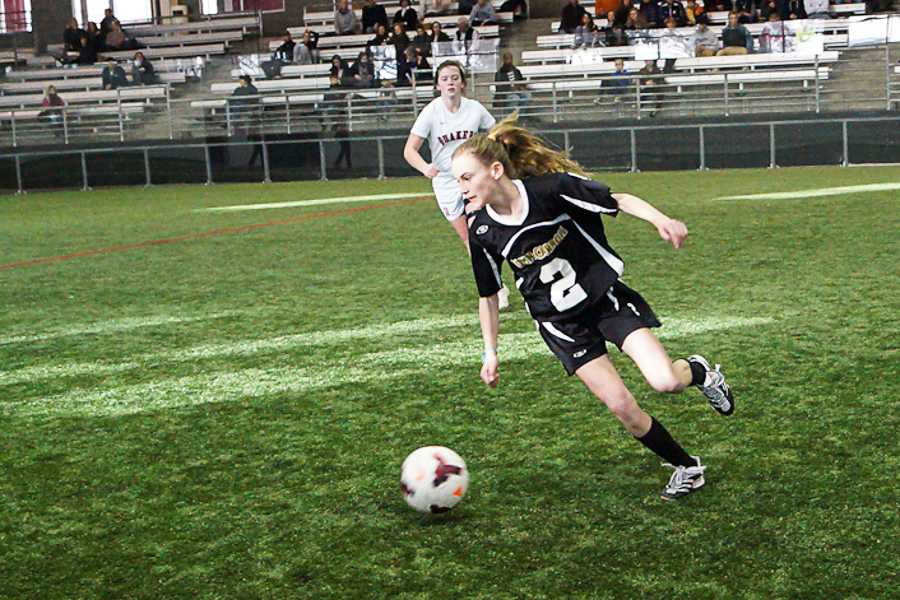 Freshman Abby Hormes kicks the ball up the field during the championship game against Friends on Feb. 8. JC lost 3-2 in overtime.