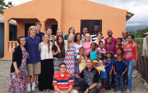 The JC Dominican Republic team stands with members of the San Juan community in front of Mary and Huber's finished house. The whole community came out that night to celebrate a house-warming party for the family.