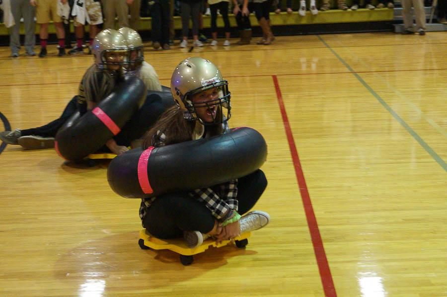 Senior McKenna McFadden races on a scooter throughout the gym as a part of a game of human curling. This was one of the actives included during the pep rally on Oct. 24.