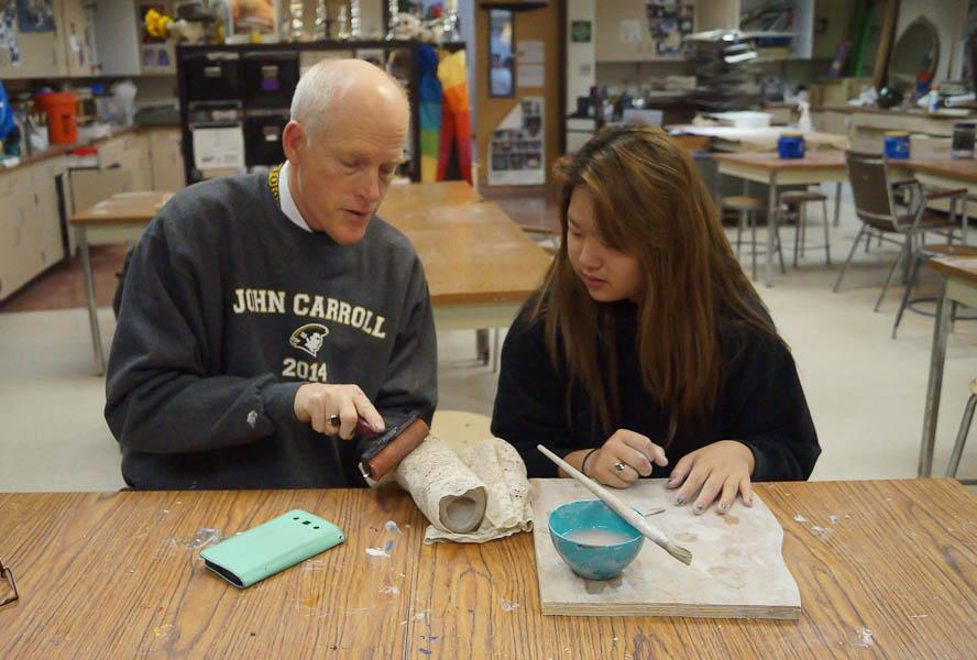 Fine arts teacher Michael Gaudreau shows senior Julia Lee how to imprint a pattern on clay for pottery. Students can go to the art wing during and after school to work on art projects.