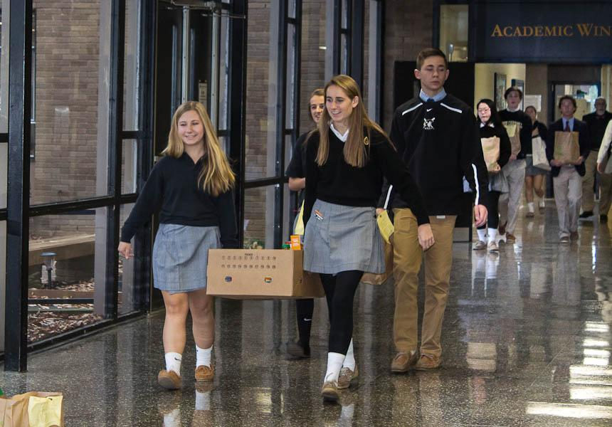 Sophomore Sydney Shupe and junior Cara Wolfarth carry a box of cans from their advisory to support the Thanksgiving food drive. The food drive occurred from Nov. 10 until Nov. 21.