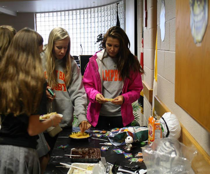 Seniors Taylor Cramer (left) and Noelle Correll (right) eat food at the Spanish Clubs Day of the Dead Fiesta. The fiesta was held on Oct. 29 in the Brown Room
