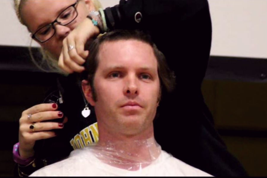 History teacher Anthony Del Puppo is shaved by senior Gabby Kropff. The head shaving event on Nov. 25 was part of a fundraiser for the Im 4 Eddie campaign, raising $21,500 for the Maynard family.