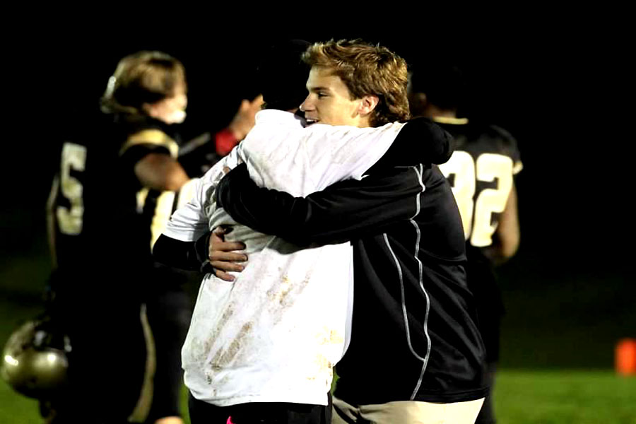 Junior Mitchell Shinnick hugs assistant head coach Bill Lewis post game after the quadruple overtime win against Boys Latin on Oct. 17. Schinnick continues to participate on the team despite the fact that he can't play due to having too many seizures.
