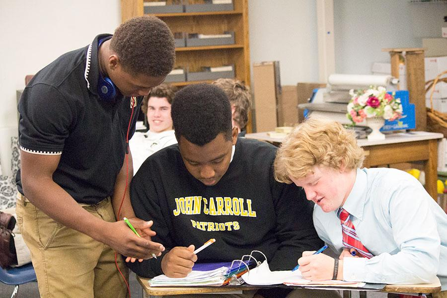 Sophomore Devin Darrington and juniors Ben Flomo and Damian Wies (left to right) help each other with homework in the library. Students can go to the library every day from 8-4:30 to work on their assignments.