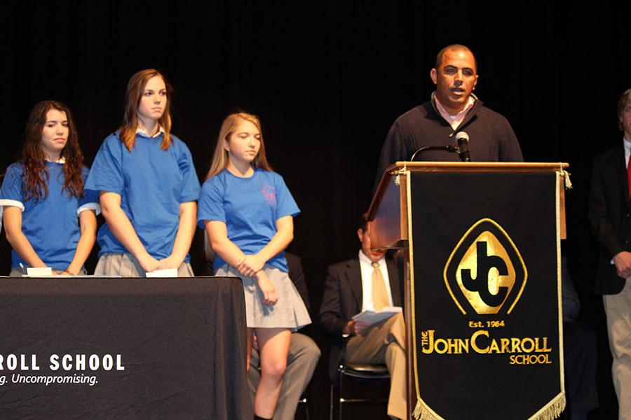 Jose Abreu, Dominican Republic native, stands at the podium with seniors Angela DeCarlo, Selena Ranney, and junior Katie Sullivan (left to right) who went on the Dominican Republic service trip last year. He came to JC to speak about his campaign Cambiando Vidas (Changing Lives).