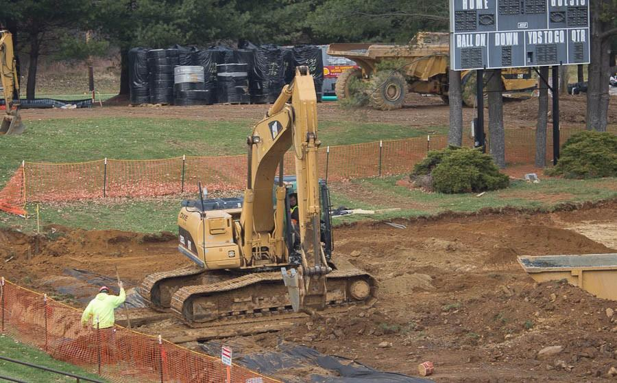 Construction workers work on building a new turf field. According to President Richard O'Hara the new target date for completion is the first week of January.