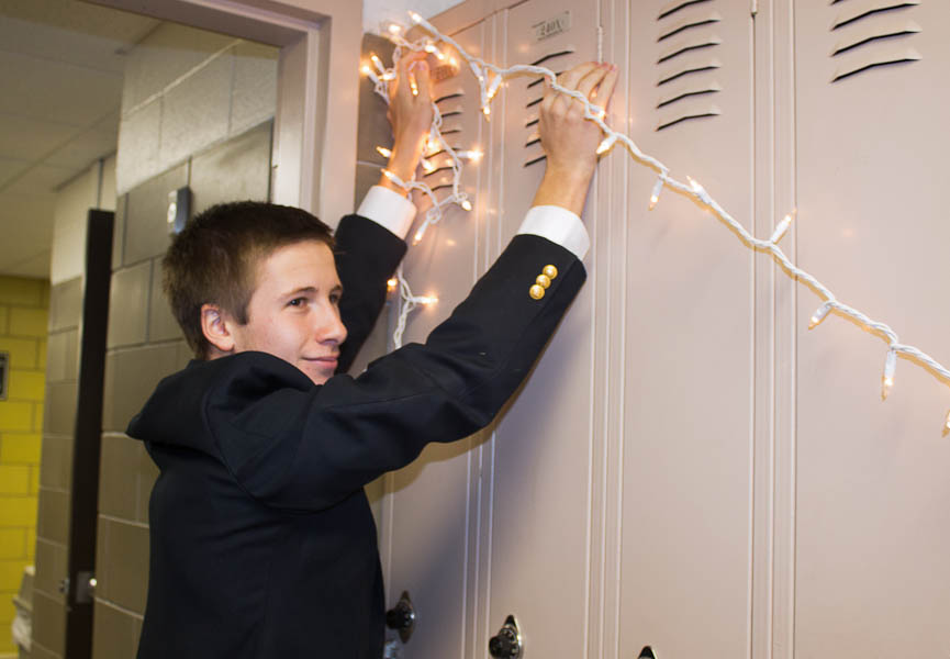 Junior+Matt+Clarke+hangs+lights+above+the+lockers+near+his+advisory.+Students+and+teachers+decorated+the+area+around+their+advisories+this+week+for+a+Christmas+door+decorating+contest.+