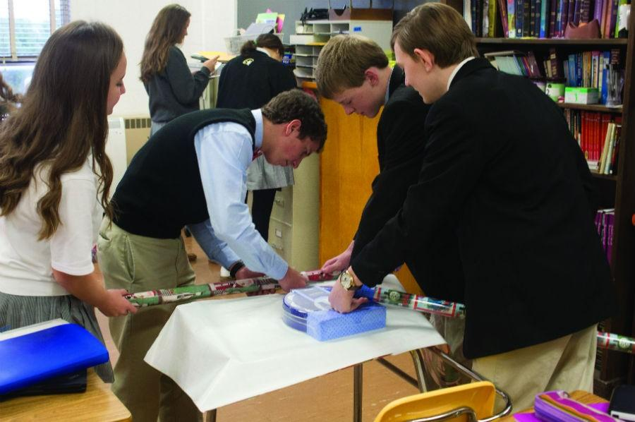 Juniors Erin Welsh and Tim Yantz, sophomore Iain Olsen, and freshman Drew Forthman (left to right) wrap presents for the Adopt-a-Family program in religion teacher Joseph Gallen's advisory. Gallen's advisory gave clothes, toys and food to their adopted family.