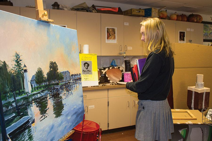 Senior Miceala Powers admires a painting in the art wing on Jan. 16. The artwork was created by art teacher Bruno Baran.