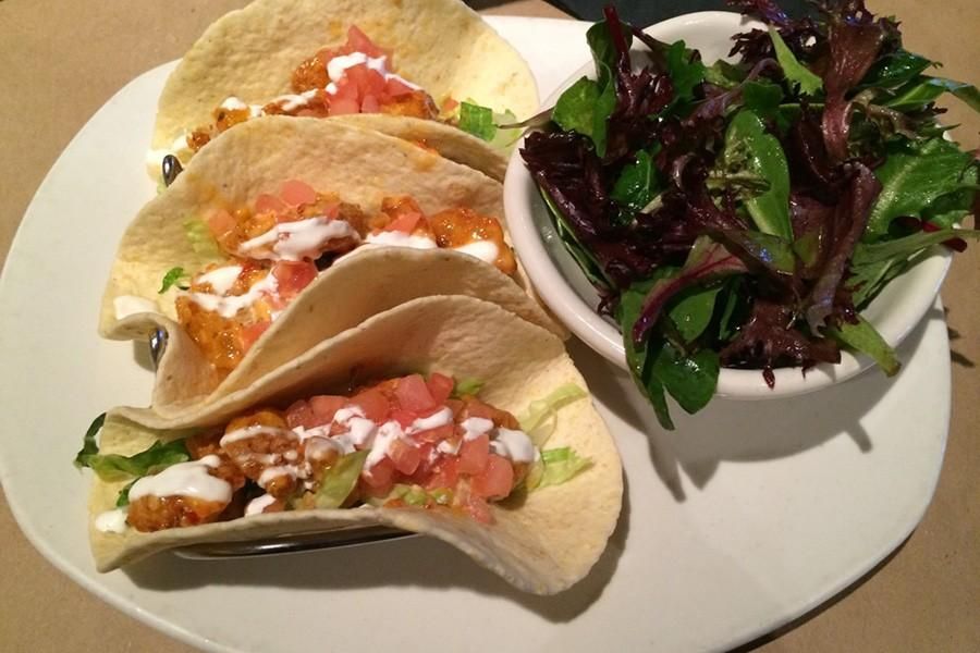 Bonefish's Bang Bang Shrimp tacos are in a soft taco shell and have lettuce and tomatoes on top of the tacos. The Bang Bang shrimp is one of Bonefish's most famous dishes.