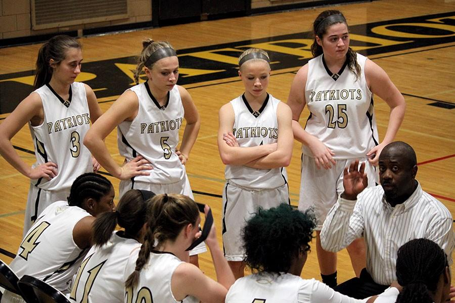 Women's varsity basketball coach Craig Simmons instructs the team on how to run their next offensive play against Archbishop Spalding. The game was Jan. 22, and the team lost 47-60.