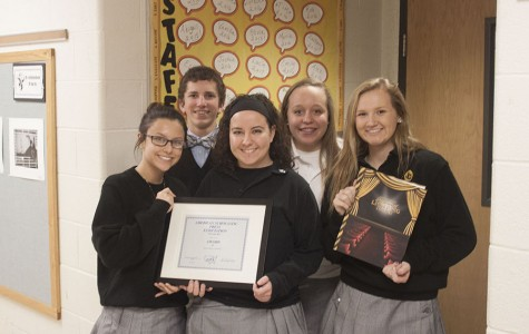 Members of last year's yearbook staff pose with one of their awards and the yearbook that won it. This year, the Pacificus won first place again in the American Scholastic Press Association's yearbook competition.