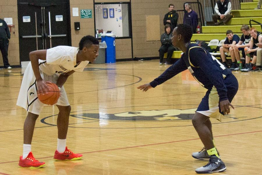 Junior guard Kevin Kangu studies the defenders on the court, searching for an opportunity. Kangu provides the role of an agile guard for the varsity basketball team.