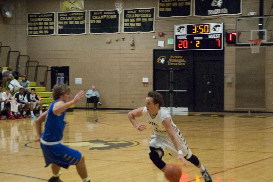 Senior guard Kimbal Mackenzie begins to drive from behind the three point line. Mackenzie's ball handling skills are a crucial part of creating scoring opportunities for the offense.