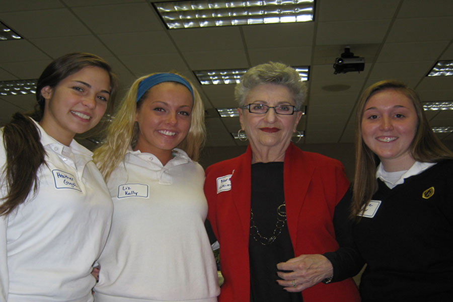 Three JC alum stand with a Holocaust survivor. In the past, Holocaust Remembrance Day was only open to seniors, but now it is open to both juniors and seniors.