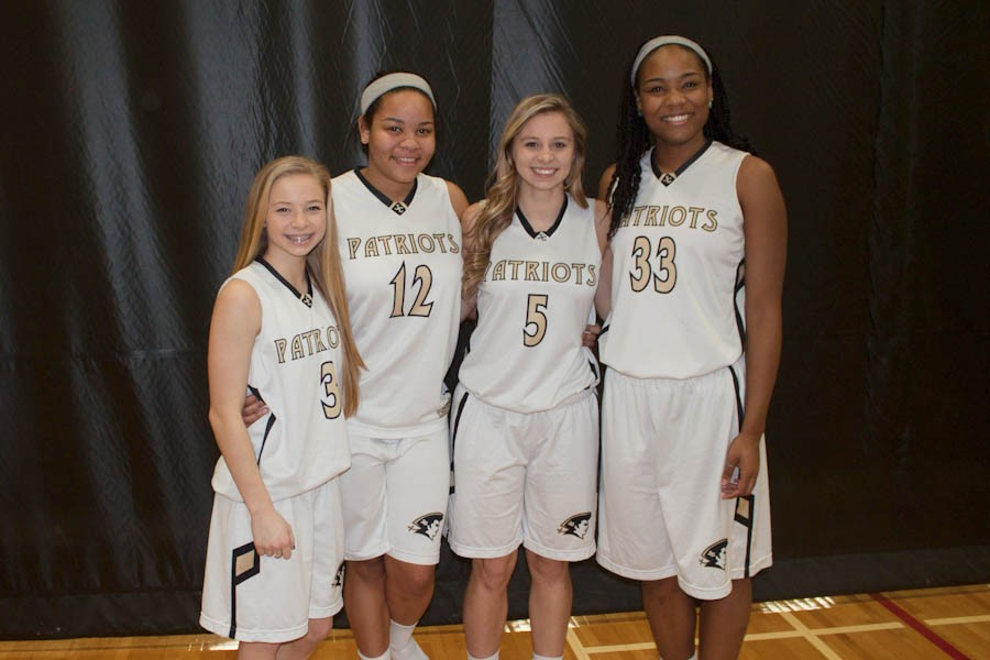 This year's varsity basketball team had two pairs of sisters filling its ranks. Freshman point guard Delaney Schutz (left) and senior point guard Madison Schutz (middle right) make up one pair, and freshman small forward Nikki Hunter (middle left) and senior center Ashley Hunter (right) compose the other.